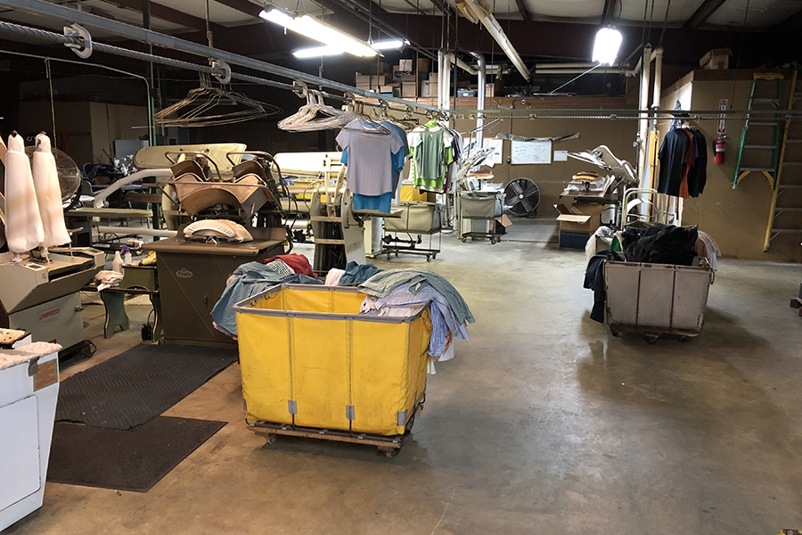 Photo of working area showing various machines used for cleaning and ironing clothing.