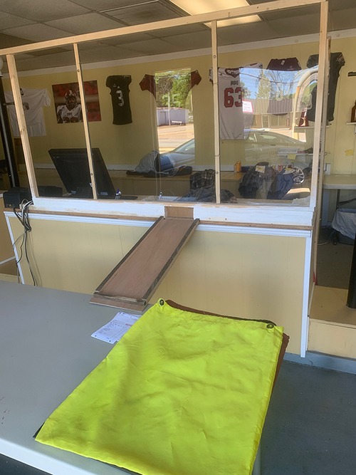 Photo of inside store front with plastic barries, drop chute and table displayed to demonstrate added protective measures.