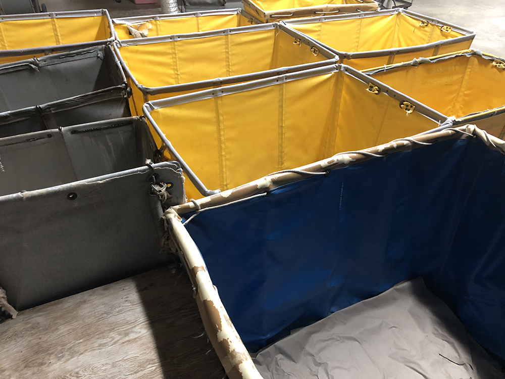 Photo of empty, yellow and blue bins for transporting clothing.